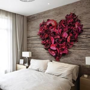 Serce usypane z płatków róż na tle drewnianej tekstury wprowadza do sypialni romantyczną atmosferę. Fot. Dekornik.
