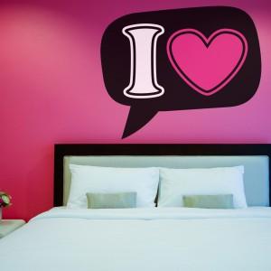 """Naklejka umieszczona na ścianie z \\\""""miłosnym motywem\\\"""" ożywia przestrzeń sypialni. Fot. Big Trix."""