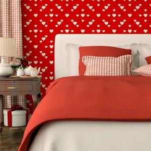Czerwona tapeta w białe, drobne serca układające się w geometryczny wzór nada sypialni wyjątkowy klimat. Fot. Minka.pl.