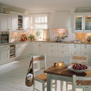 Urokliwa kuchnia w typowo klasycznym stylu. Jasne meble kuchenne zyskały ozdobne fronty i dekoracyjne, zaokrąglone uchwyty, oświetlone od wewnątrz górne szafki zostały przeszklone, a powierzchnię roboczą stanowi kamienny blat. Fot. Rational, kuchnia Chalet.