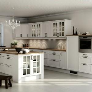 Przepiękne stylizowane meble w białym kolorze, zwieńczone drewnianym blatem. Niektóre z drzwiczek - zarówno szafek wiszących, jak i fronty wyspy kuchennej - zostały przeszklone, a szkło udekorowane dodatkowo szprosami. Fot. Nettoline, kuchnia Nordic.