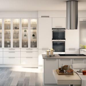 Gładkie fronty mebli kuchennych zyskują klasycyzujący charakter dzięki dużym pionowym przeszkleniom, odsłaniającym galerię zastawy stołowej, efektownie oświetlonej oświetleniem wewnątrz szafek. Fot. Marbodal.
