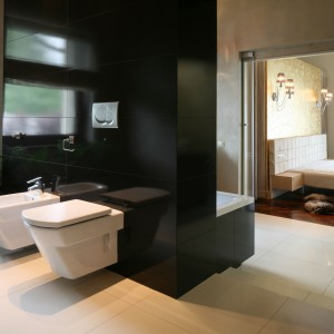 Stelaże sedesu oraz bidet zostały umieszczone na ściance dzielącej łazienkę na dwie strefy. Wykończona została czarnymi płytkami w dużym formacie. Projekt: Dominik Respondek. Fot. Bartosz Jarosz.