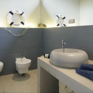 W łazience urządzonej w stylu marynistycznym, obudowa stelaży wykończona niebieskimi płytkami została dodatkowo efektownie podświetlona od góry. Projekt: Katarzyna Mikulska-Sękalska. Fot. Bartosz Jarosz.
