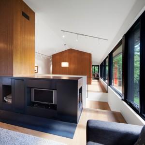 Otwartą przestrzeń strefy dziennej podzielono w oparciu o wąskie ścianki działowe. Na jednej z nich usytuowano kominek w ciemnej, geometrycznej zabudowie, w którą wpasowano również telewizor. Projekt: Blouin Tardif Architecture-Environment. Fot. Steve Montpetit.