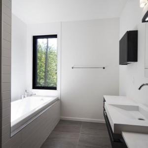 Łazienkę wykończono w monochromie i w oparciu o estetyczne, geometryczne kształty. Projekt: Blouin Tardif Architecture-Environment. Fot. Steve Montpetit.