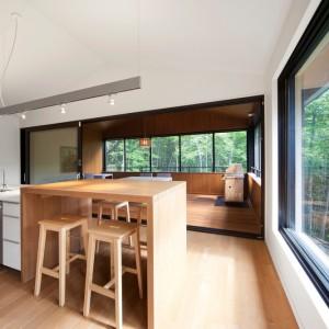 W kuchni zaplanowano również drewniany element, pełniący rolę domowego baru. Projekt: Blouin Tardif Architecture-Environment. Fot. Steve Montpetit.