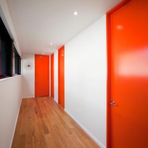 Pomarańczowe drzwi na parterze ożywiają wnętrze, stanowiąc mocny akcent kolorystyczny. Projekt: Blouin Tardif Architecture-Environment. Fot. Steve Montpetit.