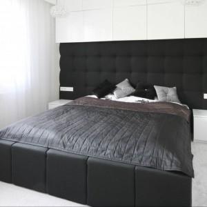 Czarna, pikowana ściana kontrastuje z jasnymi ścianami i zabudową. Jej kolorystykę dobrano do ramy łóżka. Projekt: Dominik Respondek. Fot. Bartosz Jarosz.