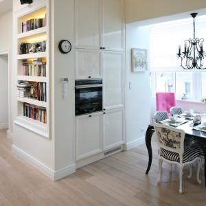 Wąska ścianka pomiędzy salonem a kuchnią stała się dobrym miejscem na wyeksponowanie książek. Biblioteczka w nieco eleganckim klasycznym otoczeniu. Projekt: Małgorzata Galewska. Fot. Bartosz Jarosz.