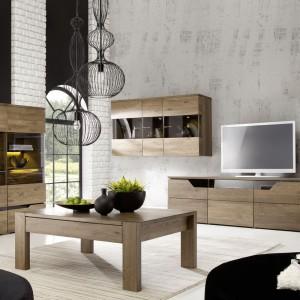 Drewniane meble do salonu ocieplają biel ceglanej ściany. Takie połączenie zawsze wygląda stylowo. Fot. Meble Matkowski.