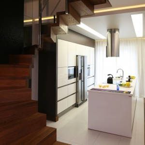 Schody usytuowane między kuchnią a salonem stanowią pewną naturalną granicę miedzy tymi dwoma wnętrzami. Projekt: Chantal Springer. Fot. Bartosz Jarosz.