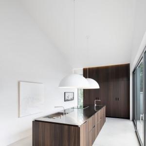 Wyspę umeblowano w minimalistycznym stylu - na jasnym tle ścian i podłogi, wyeksponowane są wyspa i zabudowa w czekoladowym kolorze. Projekt: Thomas Balaban Architecture. Fot. Adrien Williams.