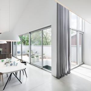 Duże przeszklenia dostarczają dzienne światło do wnętrz, które odbija się od białych ścian, rozświetlając wnętrze i nadając mu optymistyczny charakter. Projekt: Thomas Balaban Architecture. Fot. Adrien Williams.
