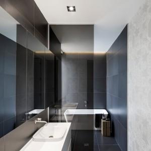 Monochromatyczna, czarno-biała łazienka została zamknięta w geometryczne, minimalistyczne formy. Projekt: Thomas Balaban Architecture. Fot. Adrien Williams.