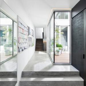 Betonowa podłoga i ciemna ściana idealnie wpisują się w nowoczesny ton domu i idealnie korespondują z dużymi przeszkleniami. Projekt: Thomas Balaban Architecture. Fot. Adrien Williams.