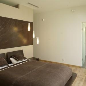 Nic nie zakłóca nowoczesnego charakteru tej sypialni. Proste jest łóżko, oświetlenie i dekoracja na ścianie. Do tego stonowana, spokojna kolorystyka. Projekt: Maciej Matkowski. Fot. Bartosz Jarosz.