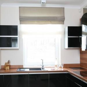 Ścianę nad płytą grzejną pokryto panelem z drewnianym dekorem, a wolną przestrzeń okalającą okno nad zlewozmywakiem wykorzystano na montaż dwóch niewielkich szafek. Projekt: Karolina Łuczyńska. Fot. Bartosz Jarosz.
