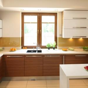 Górne szafki w dwóch kolorach - korpusy pokryte drewnianym dekorem, a fronty wykończone na wysoki połysk i utrzymane w bieli. Projekt: Magdalena Bonin-Jarkiewicz. Fot. Bartosz Jarosz.