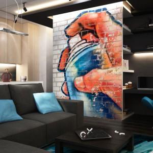 Fototapeta przedstawiająca graffiti z dłonią, która tworzy na ścianie kolejny rysunek. Ten oryginalny wzór będzie doskonały do nowoczesnego wnętrza w stylu industrialnym, ale nie tylko. Fototapeta dostępna na stronie Fixar. Fot. Fixar.