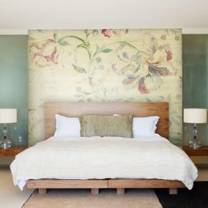 Elegancka tapeta w okazałe kwiaty, naklejona za wezgłowiem łóżka zmieni zwykłą sypialnie w oazę wiosennego wypoczynku. Tapeta z serii Classic marki JVD. Fot. JVD.