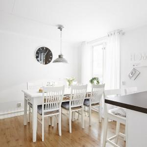 Jadalnia niemal w całości jest biała - od ścian, przez stół i krzesła. Mocniejszym akcentem kolorystycznym jest czarny zegar. Fot. Vastanhem.