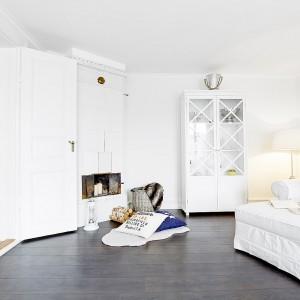 Ciemna podłoga w salonie efektownie kontrastuje z białymi ścianami i meblami. Fot. Vastanhem.