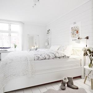 Sypialnia jest całkowicie biała. Ściany i podłogę pokrywają deski pomalowane na biało, białe jest również łóżko. Ozdobiono je kwiecistymi tekstyliami, które nadają wnętrzu romantycznego charakteru. Fot. Vastanhem.