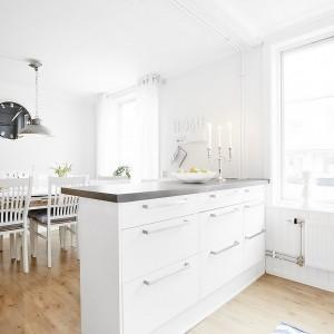 Kuchnię od jadalni oddziela półwysep, wyposażony w liczne szuflady. Biały mebel wieńczy kontrastujący, ciemny blat. Fot. Vastanhem.