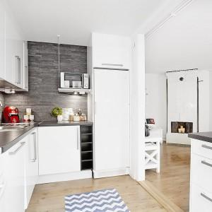 Funkcjonalna kuchnia to zabudowa w kształcie litery L oraz praktyczny półwysep. Całość wykończono w bieli, choć zdecydowano się również na ciemniejszy akcent kolorystyczny na ścianach nad blatem oraz na samym blacie. Fot. Vastanhem.