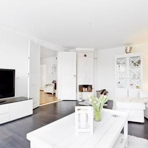 Z salonu do sąsiedniego pomieszczenia prowadzą podwójne drzwi, charakterystyczne dla starego budownictwa. W atmosferę przeszłości wpisuje się również piękny, przeszklony regał. Fot. Vastanhem.