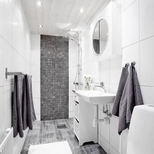 Biało-szara łazienka wybija się delikatnie z panującej w całym mieszkaniu stylistyki. Tutaj więcej jest ciemnoszarych akcentów. Strefę prysznica i powierzchnię nad wc wykończono ciemnoszarymi płytkami. Fot. Vastanhem.