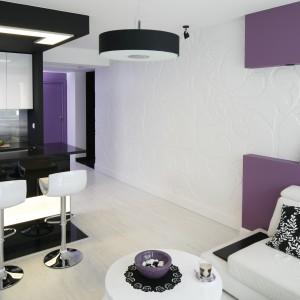 Ciekawym kontrastem dla jasnego, delikatnego salonu jest czarno-biała kuchnia na wysoki połysk sąsiadująca z przestrzenią wypoczynkową. Projekt: Joanna Ochota. Fot. Bartosz Jarosz.
