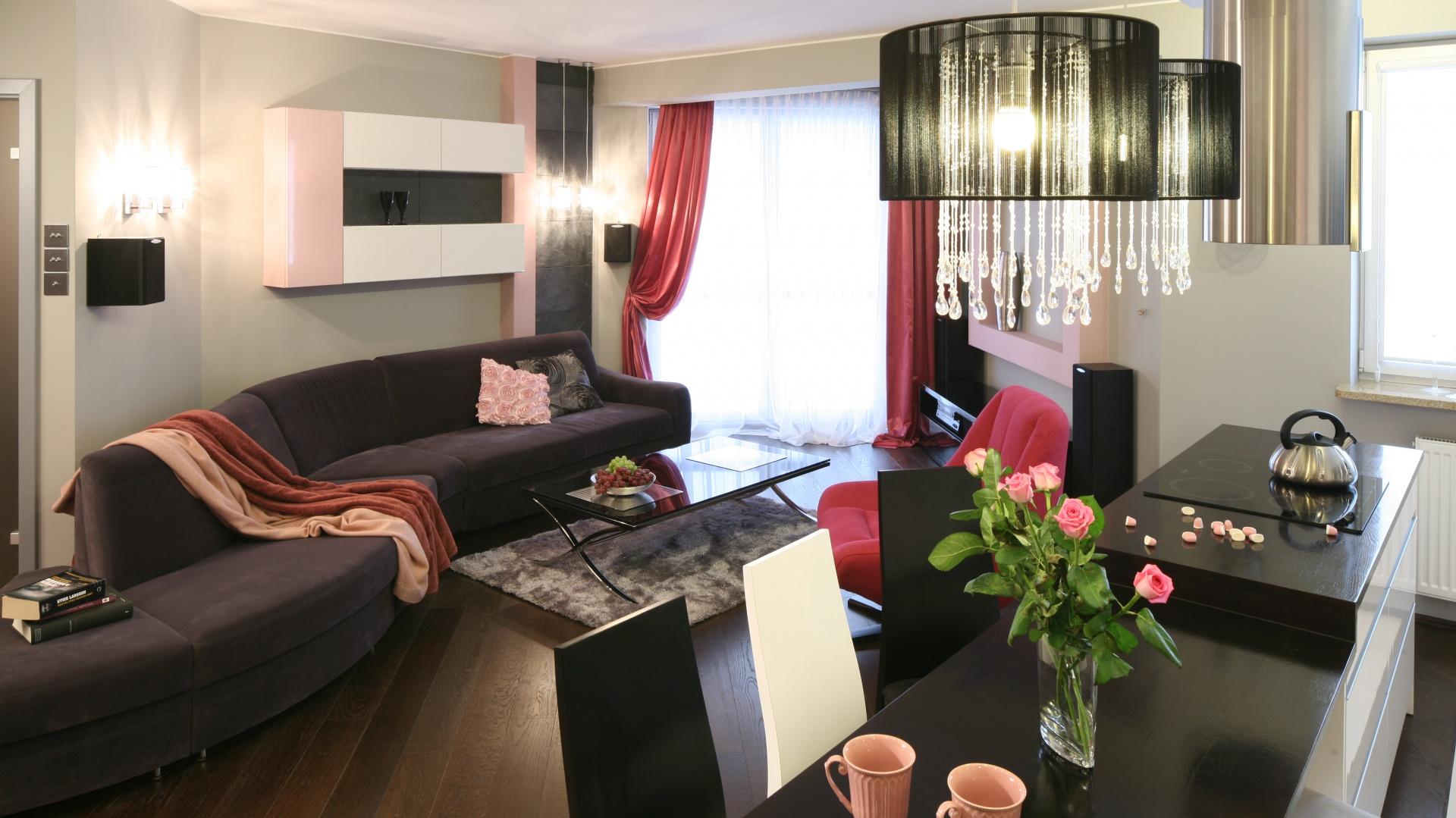 Na szczególną uwagę zasługuje śliwkowa kanapa o niestandardowym kształcie. Forma mebla pozwala do maksimum wykorzystać przestrzeń w salonie. Projekt: Marta Dąbrowska. Fot. Bartosz Jarosz.