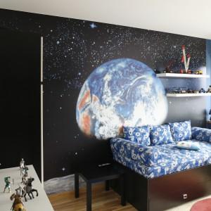 Największą dekoracją, a zarazem detalem, który wyznacza charakter całej aranżacji jest kosmiczna fototapeta zdobiąca ścianę nad łóżkiem. Dekoracja przedstawiająca naszą planetę z perspektywy milionów lat świetlnych w towarzystwie tysięcy gwiazd sprawia, że pokój chłopca, wygląda bardzo oryginalnie. Projekt: Anna Gruner. Fot. Bartosz Jarosz.
