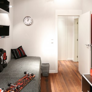 Dość wąski pokój w kształcie prostokąta opanowało modne trio kolorystyczne: czerni, bieli i czerwieni. Dzięki temu powstało wnętrze funkcjonalne, młodzieżowe i stylowe. Idealne dla nastoletniego chłopaka. Projekt Katarzyna Mikulska-Sękalska. Fot. Bartosz Jarosz.