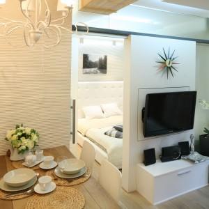 Część sypialnianą od salonu oddziela ścianka z telewizorem, która dzięki swojej konstrukcji obraca się o 360 stopni, pozwalając tym samym oglądać telewizję w obu pomieszczeniach, ale nie jednocześnie. Projekt: Łukasz Sabat. Fot. Bartosz Jarosz.