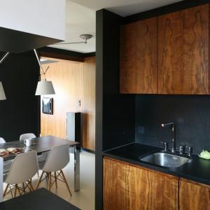 Piękna, nowoczesna kuchnia, nawiązująca do minimalizmu amerykańskich lat 50-tych. Drewno w minimalistycznej odsłonie zestawiono z czarnymi powierzchniami. Projekt: Michał i Kasia Dudko. Fot. Bartosz Jarosz.