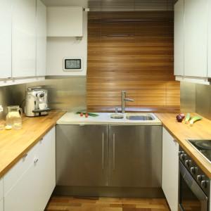 Ta niewielka kuchnia zyskała białe, optycznie powiększające przestrzeń, fronty oraz akcenty w kolorze drewna, które ocieplają aranżację. Blat kuchenny i roleta nad zlewem harmonizują z parkietem nad podłodze. Projekt: Marcin Lewandowicz. Fot. Bartosz Jarosz.