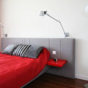 Szary tapicerowany zagłówek jest dokładnie w takim samym kolorze jak rama łóżka. Doskonale pasuje zarówno do jasnej ściany, jak i czerwonych akcentów ożywiających sypialnie. Projekt: Iza Szewc. Fot. Bartosz Jarosz.