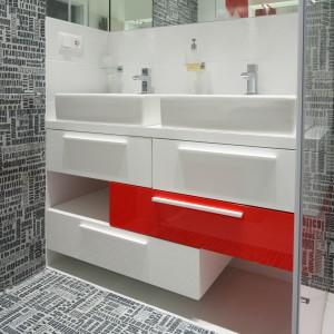 Poza jedną czerwoną szufladą prawie cała szafka podumywalkowa jest biała. Czerwone akcenty ożywiają nowoczesną łazienkę urządzoną w bieli i szarości.  Projekt: Katarzyna Mikulska-Sękalska. Fot. Bartosz Jarosz.