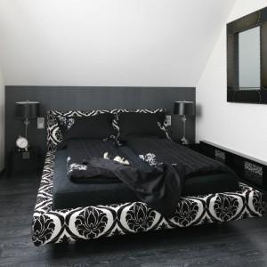 Czarno biała sypialnia na poddaszu prezentuje się bardzo elegancko. Tapicerowane dekoracyjną tkaniną łóżko to niebanalny element wnętrza. Projekt: Małgorzata Borzyszkowska. Fot. Bartosz Jarosz.