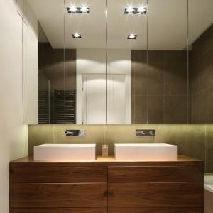 Szafki wiszące nad umywalkami sięgają aż do sufitu. Są pojemne i praktyczne, a przy tym dodają wnętrzu głębi. Projekt: Agnieszka Ludwinowska. Fot. Bartosz Jarosz.