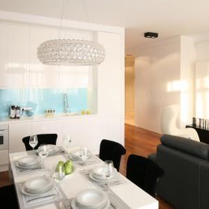 Biel, szarości oraz drewno to główne kolory w całym apartamencie. W kuchni wprowadzono barwny akcent w postaci tafli szkła polakierowanej na błękit. Fot. Bartosz Jarosz.