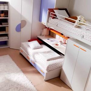 Szafa narożna w praktyczny sposób pozwoli wykorzystać nieustawny kąt w pomieszczeniu. Oprócz niej, każda z dziewczynek ma osobną szafę, znajdującą się na wysokości łóżka. Fot. Doimo Cityline.