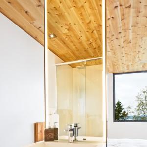 Sypialnie w stylu master połączono z łazienkami w efektowny wizualnie sposób. Od strefy spania, łazienkę oddziela niewielka ścianka, na której zlokalizowano umywalkę. Pozostałą powierzchnię ściany pokryto długim lustrem. Projekt: MU Architecture. Fot. Ulysse Lemerise Bouchard.