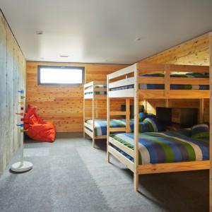 W piwnicy dużego domu urządzono pokój dla dzieci. Atmosfera internatu sprzyja integracji i zabawie najmłodszych. Projekt: MU Architecture. Fot. Ulysse Lemerise Bouchard.