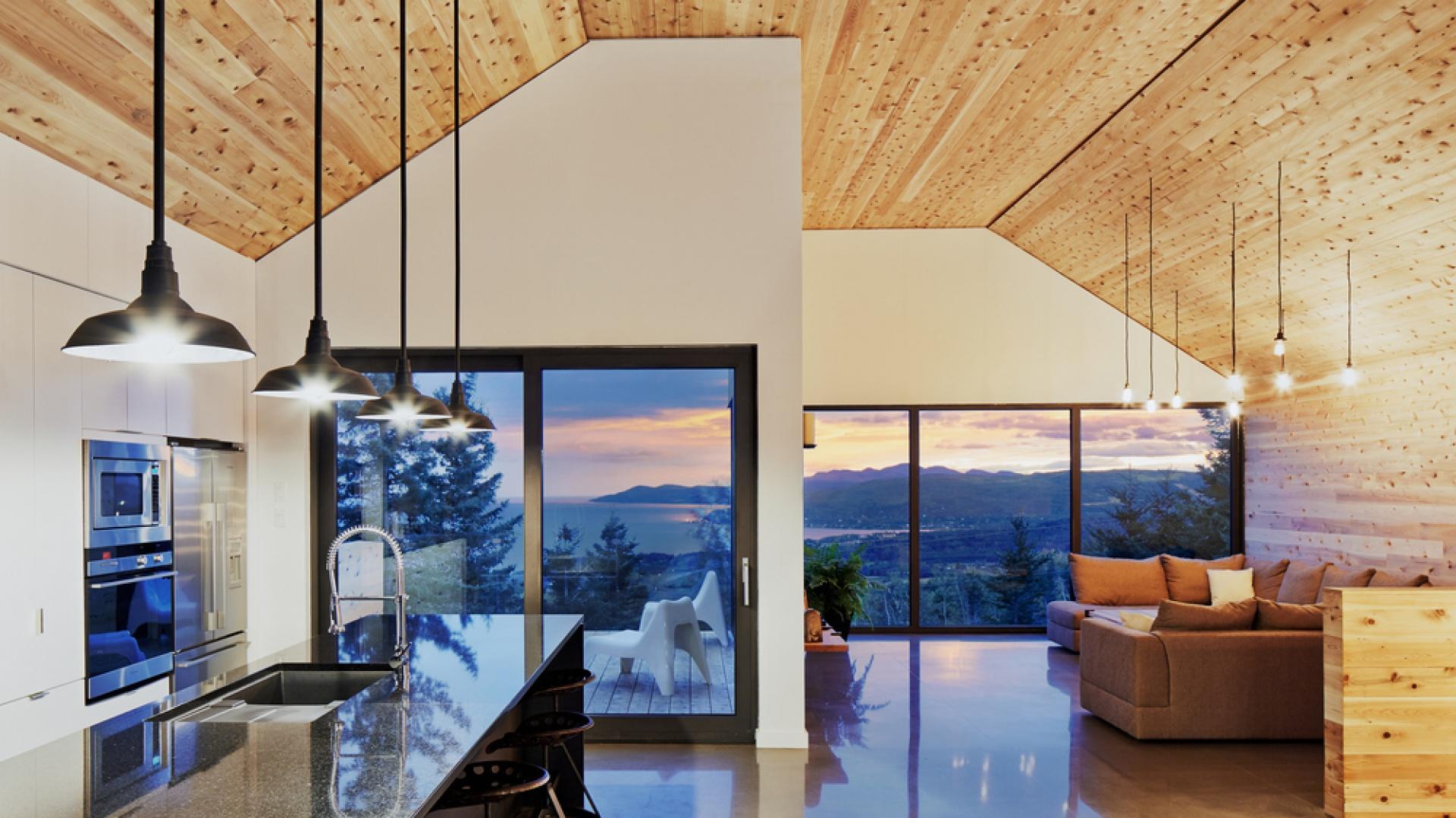 Strefę dzienną urządzono na ostatniej kondygnacji domu, tak aby goście mogli podziwiać w pełni, otaczające dom krajobrazy. W pomieszczeniu znalazły się salon, jadalnia i nowoczesna kuchnia z wyspą i wysoką, wpasowaną w ścianę, zabudową. Projekt: MU Architecture. Fot. Ulysse Lemerise Bouchard.