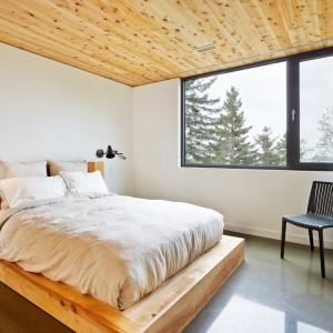 Na parterze domu usytuowano strefę z sypialniami. Wewnątrz panuje schludny, oszczędny wystrój, który ociepla drewno na suficie. Drewniany jest również panel za łóżkiem, służący za zagłówek. Projekt: MU Architecture. Fot. Ulysse Lemerise Bouchard.