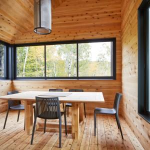Materiałem dominującym w strefie jadalni jest drewno cedrowe. Pięknie harmonizuje ze stołem i wydobywa ciemny kolor ram okiennych. Projekt: MU Architecture. Fot. Ulysse  Lemerise Bouchard.